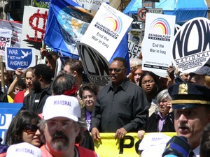 Thumbnail of Jesse Jackson in the midst of the crowd of antiwar marchers in the streets of             New York, with signs and banners opposing the war in Iraq Taken during the March for Peace, Justice and Democracy