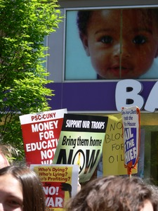 Thumbnail of Antiwar marchers in the streets of New York with signs and banners opposing the             war in Iraq, passing by a Toys R Us store with images of babies Taken during the March for Peace, Justice and Democracy