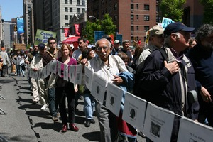 Thumbnail of Marchers carrying a long string of photos of soldiers killed in Iraq, during the protest against the war in Iraq Taken during the March for Peace, Justice and Democracy