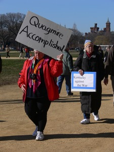 Thumbnail of Protester on the National Mall, marching against the War in Iraq, carrying sign             reading 'Quagmire accomplished'