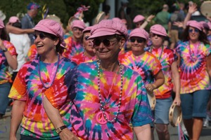 Thumbnail of Parade marchers in tie-dye shirts and pink hats : Provincetown Carnival parade
