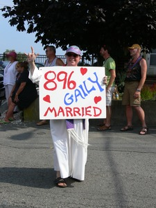 Thumbnail of Parade marcher with sign celebrating same sex marriage, reading '896 gaily married' : Provincetown Carnival parade