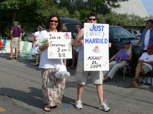 Thumbnail of Parade marchers with signs celebrating same sex marriage reading 'Join us             tomorrow 3 PM UU' and 'Just (about) married' : Provincetown Carnival parade