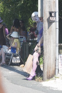 Thumbnail of Parade goer in faux fishnet stockings leaning against a telephone pole : Provincetown Carnival parade