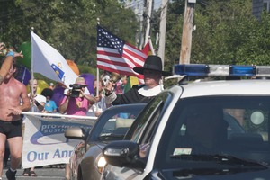 Thumbnail of Police escort leading the approaching parade, with man dressed in Puritan             costume ringing a bell : Provincetown Carnival parade