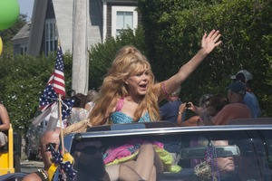 Thumbnail of Grand Marshall Charo riding in the parade, waving to the crowd : Provincetown Carnival parade