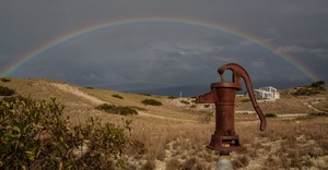 Thumbnail of Water pump set against a rainbow over the dunes at Fowler Dune Shack, Provincetown