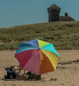Thumbnail of Woman with an umbrella pitched on the beach, with the life saving station in the             background, Provincetown