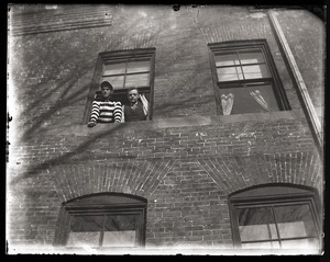 Thumbnail of Two students looking out of a South College dorm             window, Massachusetts Agricultural College