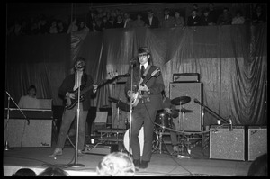 Thumbnail of The  Byrds on stage at Curry Hicks Cage L. to r.: Gram Parsons (organ), Chris Hillman (bass), Kevin Kelley (drums,             obscured), Roger McGuinn (guitar)