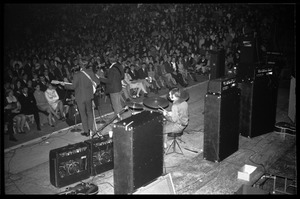 Thumbnail of The  Byrds on stage at Curry Hicks Cage View from behind stage: l. to r.: Roger McGuinn (guitar), Chris Hillman             (bass), Kevin Kelley (drums)