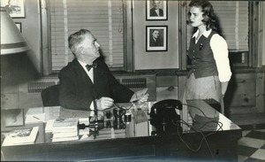 Thumbnail of Hugh P. Baker at his office desk and speaking with student
