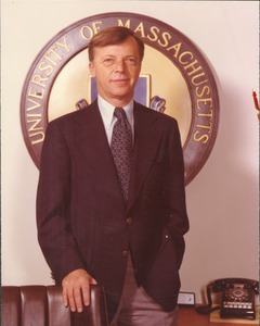 Thumbnail of David C. Knapp standing behind desk in front of University of Massachusetts logo