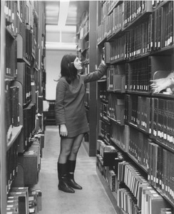 Thumbnail of Cindy Olken standing in library, pulling book out of stacks