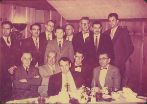 Thumbnail of Faculty members gathered behind a dining table