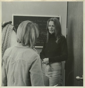 Thumbnail of Joan P. Bean standing indoors, talking to student