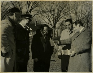 Thumbnail of Randolph W. Bromery, Allen Torrey, Fire Chief Doherty,             Mike Sullivan, and Jack Littlefield, standing outdoors reading a paper