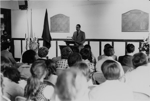 Thumbnail of Randolph W. Bromery standing indoors, behind podium, before an audience