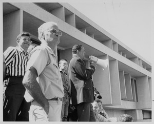 Thumbnail of Randolph W. Bromery standing outdoors, speaking into bullhorn