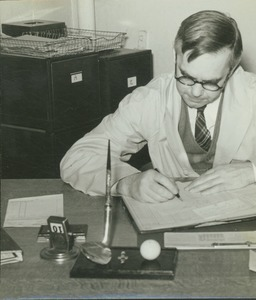 Thumbnail of Professor Lawerence S. Dickinson sitting indoors, working behind desk