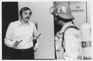 Thumbnail of Bud Fay, Amherst Hockey Team Coach, standing indoors, talking with fireman