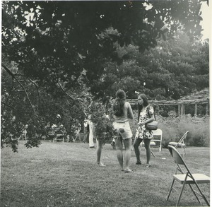 Thumbnail of Katie Gillmor standing outdoors, talking with two female student