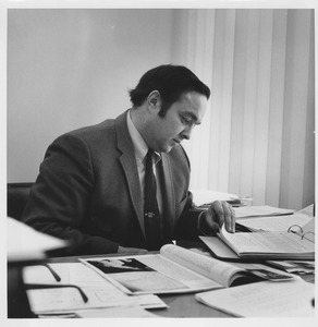 Thumbnail of Robert L. Gluckstern sitting indoors, working behind desk