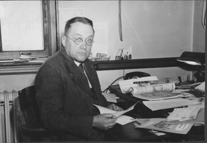 Thumbnail of Harold M. Gore sitting indoors, behind desk
