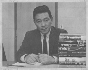 Thumbnail of Richard E. Kim sitting at a desk with books