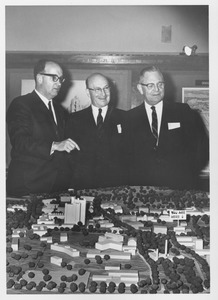 Thumbnail of Dean Edward C. Moore with two unidentified men standing above a scale model of the             Umass campus
