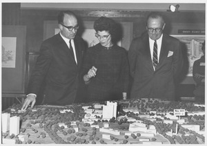 Thumbnail of Dean Edward C. Moore with an unidentified woman and man standing above a scale model of the             Umass campus