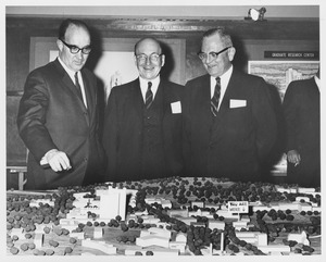 Thumbnail of Dean Edward C. Moore with two unidentified men gesturing towards a scale model of the             Umass campus