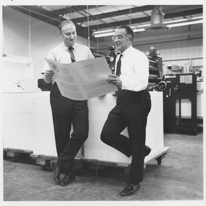 Thumbnail of Edwin Rossman and unidentified man examining a print run in press room
