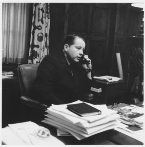 Thumbnail of John William Ryan seated at office desk, talking on telephone