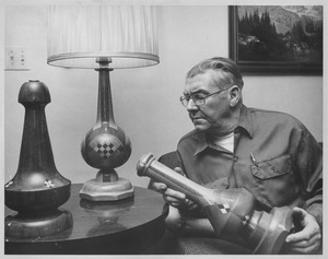 Thumbnail of John Ryan sitting with handcrafted lamps