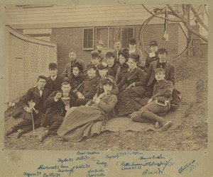 Thumbnail of Group of students sitting on a blanket on the grass with a building and a             penny-farthing bicycle in the background