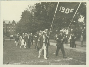 Thumbnail of Members of the class of 1905 walking outside and holding a 1905 banner