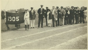 Thumbnail of Members of the class of 1905 standing outside in a line behind a 1905 banner on a track