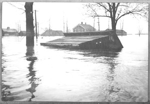 Thumbnail of Building toppled and partially submerged by floodwaters