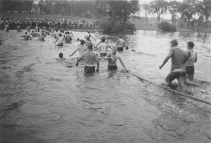 Thumbnail of Rope pull participants wade through campus pond