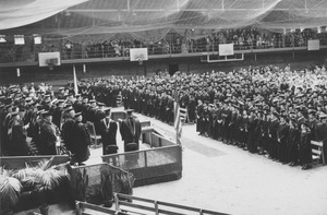 Thumbnail of Graduates, guests and faculty stand during commencement exercises
