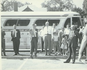 Thumbnail of Alumni Medal recipients and family stand in front of a bus during Centennial Alumni weekend