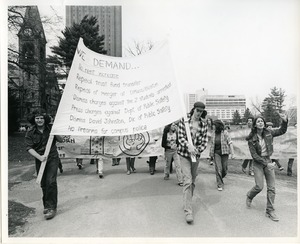 Thumbnail of Board of Trustees fee increase demonstration: Charles Bagli (l) and protestors with sign and banner marching from the Student Union to the Whitmore Administration Building