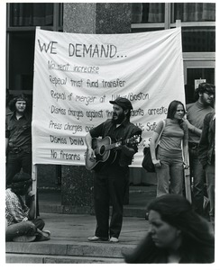 Thumbnail of Board of Trustees fee increase demonstration: man playing guitar with protestors on the steps of the Student Union, Charles Bagli holding sign (l)