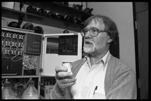 Thumbnail of Louis Carpino standing in front of lab equipment, bottle in hand