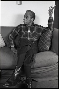 Thumbnail of James Baldwin Baldwin seated on a sofa, talking