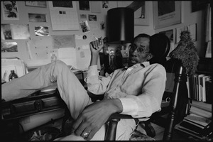 Thumbnail of Julius Lester at home: Lester reclining in his office with a cigarette