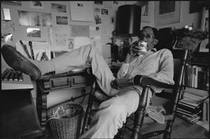 Thumbnail of Julius Lester at home: Lester reclining and holding a mug in his office