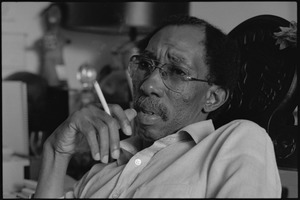 Thumbnail of Julius Lester at home: Lester holding a cigarette