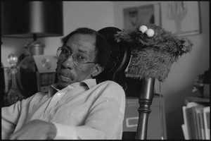 Thumbnail of Julius Lester at home: Lester seated next to a Cookie Monster puppet
